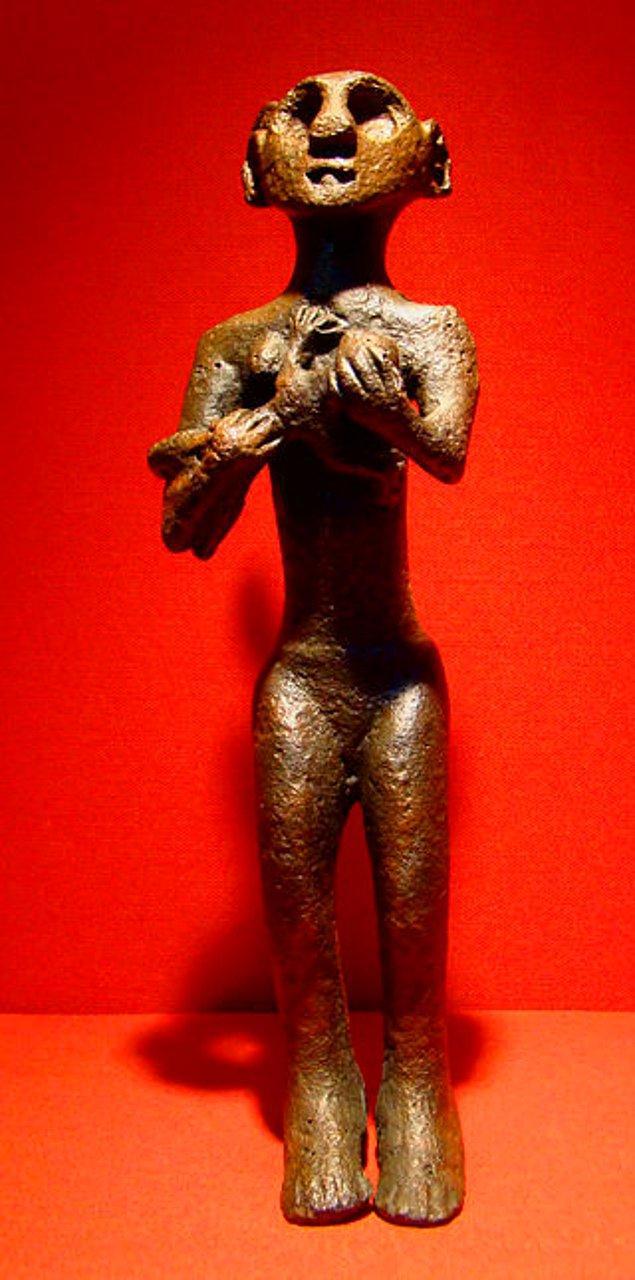 12. Horoztepe'de bir mezarda bulunan bebek emziren bronz çıplak kadın heykeli.