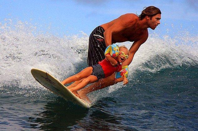 Отец учит свою дочь серфингу.