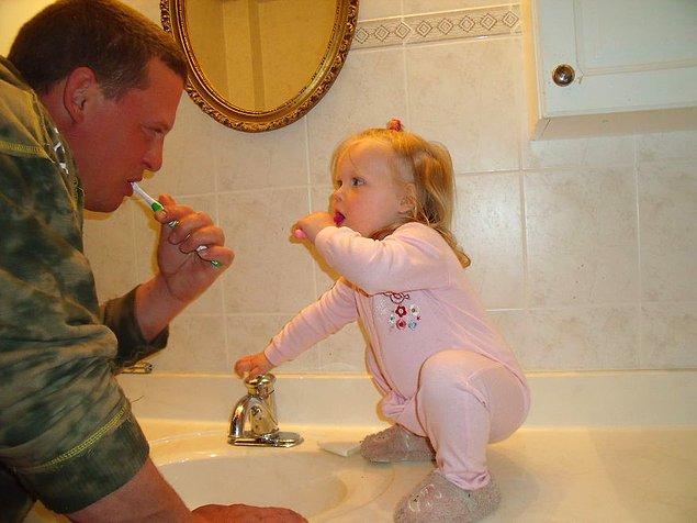 Отец пытается научить маленькую дочь чистить зубы.