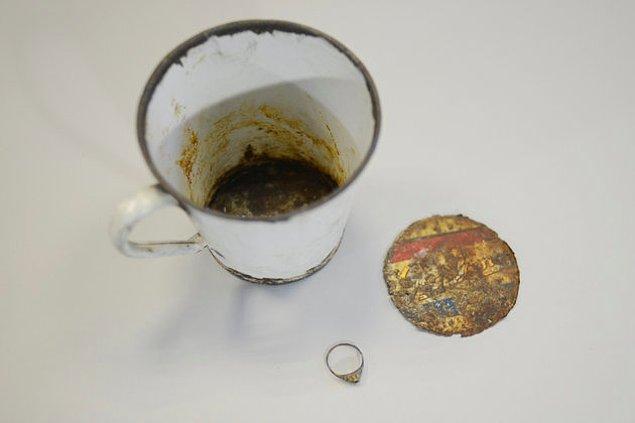 Polonya'daki Auschwitz Müzesi çalışanları, eski bir kulplu bardağın altına saklanmış bir yüzük ve kolye keşfettiler.