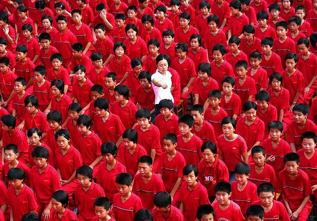 9. Yaklaşan Çin Ulusal Günü için kırmızı giyinen ortaokul öğrencileri ve aralarında yürüten öğretmen.