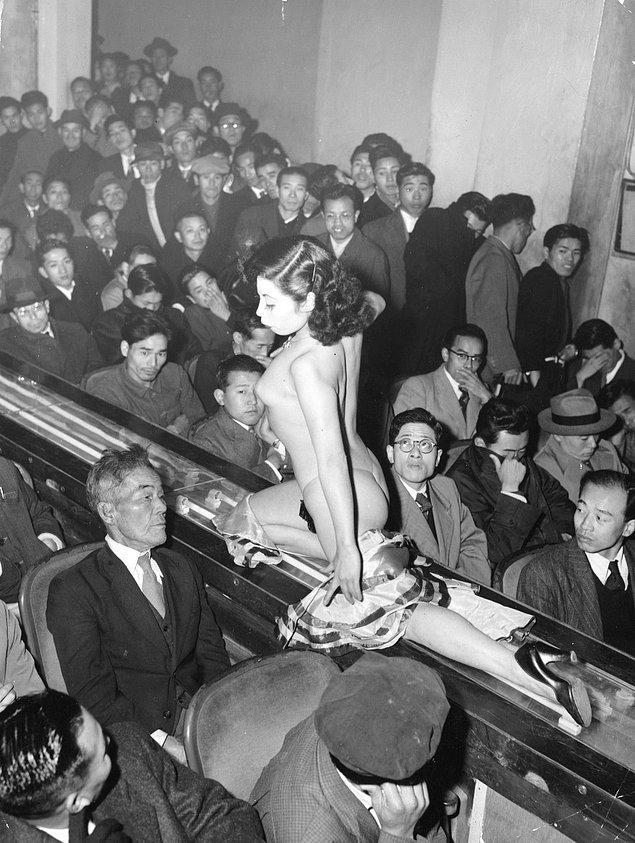 22. Tokyo striptiz şovunda ışıklı bir geçit üzerinde performansını sergileyen bir striptizci, 1957.