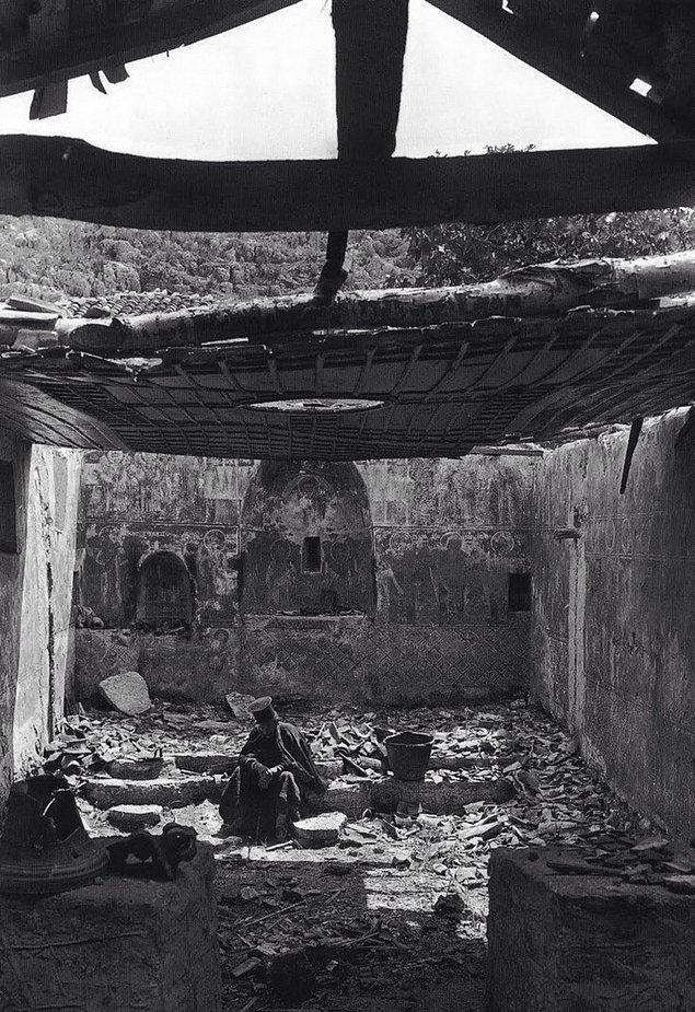 27. Bir Yunan Ortodoks papazı Balkan Savaşı sırasında tahrip edilmiş kilisesinin içinde otururken, Yunanistan, 1913.