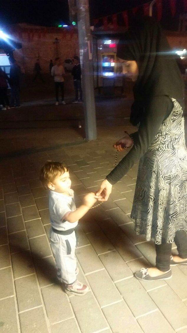 4 -5 yaşlarındaki çocuğunun kaybolmasını önlemek isteyen Arap kadın turist, çocuğunu kolundan kalın bir iple bağlayıp gezdirdi
