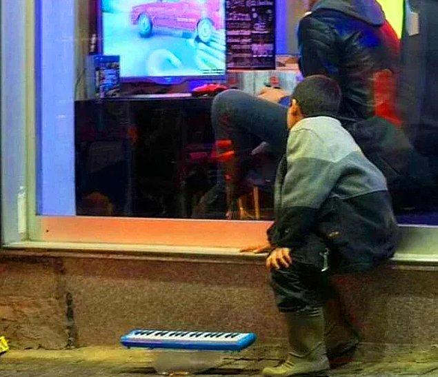10. Sokakta çalışmak zorunda olan ama içeride oyun oynayanları görünce tüm dikkati oraya yapışıp kalan bu küçük çocuğu hemen görüp aralarına alan bu abileri