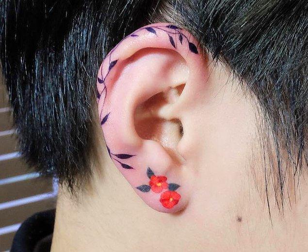 1. Koreli dövme sanatçısı Zihee'nin, kulak kıkırdağını saran bir asma ve küpe gibi duran iki çiçekten oluşan eseri.