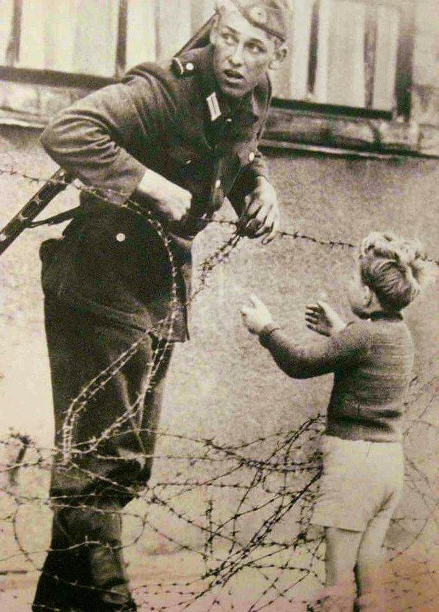 25. Doğrudan emirlere karşı gelerek, yeni kurulan Berlin Duvarı sebebiyle ailesinden ayrı düşmüş küçük çocuğun çitlerden geçmesine yardım eden Alman askeri, 1961.