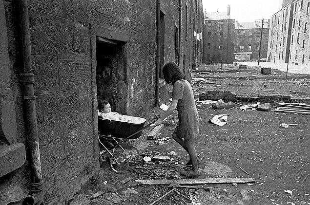14. Fakir ailelerin elektrik ve su olmadan yaşamaya çalıştığı bir bölge olan Gorbals enkazında bebek arabasını evine süren genç bir anne, Glasgow, İskoçya, 1970.