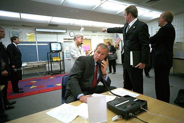 2. George Bush'un asistan yardımcısı Dan Bartlett, Başkan Bush yeni güvenlik bilgilerini dinlerken ona haberleri gösteriyor.