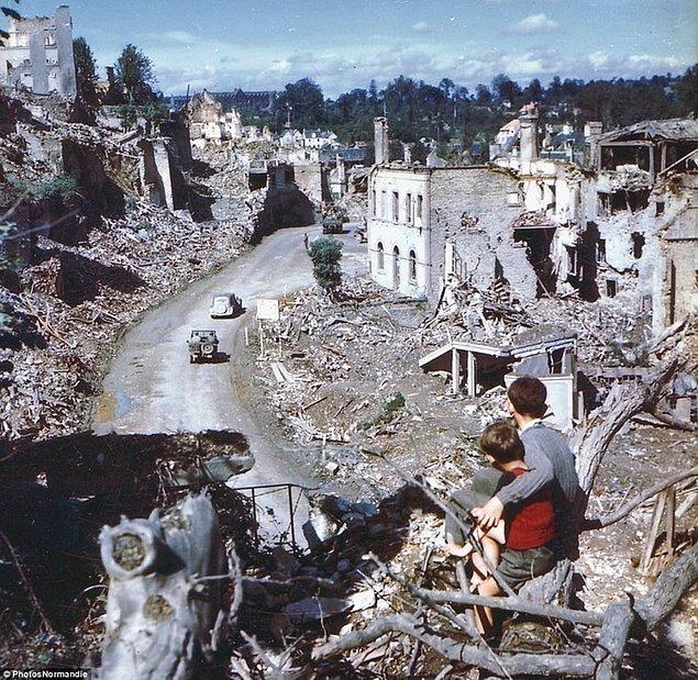 14. İki Fransız çocuk bir tepeden, Müttefik araçlarının yıkılmış olan binaların arasında geçişini izlerken, 1944.