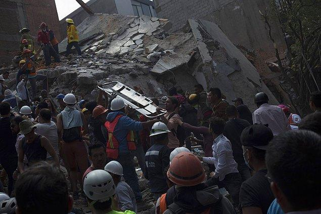 Yıkılan binanın altında kalan çalışanları kurtarabilmek için cankurtaranlardan oluşan insan zinciri bir sedyeyi elden ele geçirirken görüntülenmiş.