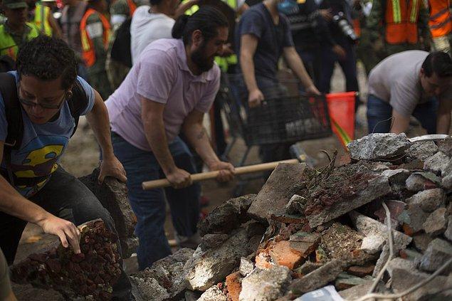 Gönüllüler moloz yığınlarını çıplak elle kaldırarak aşağıdaki insanları kurtarmaya çabalıyor...
