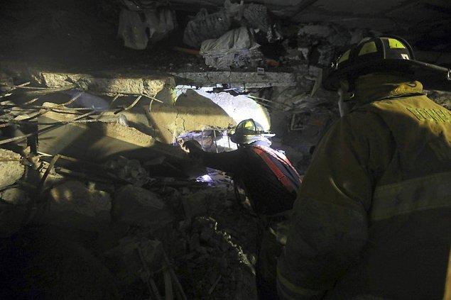 İtfaiye ekipleri yıkılan binanın altında kalan insanlardan yaşadıklarına dair bir işaret beklerken görüntülenmiş.