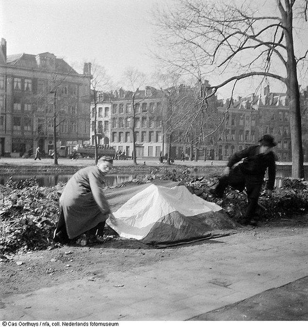 11. Hollandalı direniş üyeleri, 30 arkadaşının idam edildiği alana Hollanda bayrağı sererken, Amsterdam, Mart 1945.