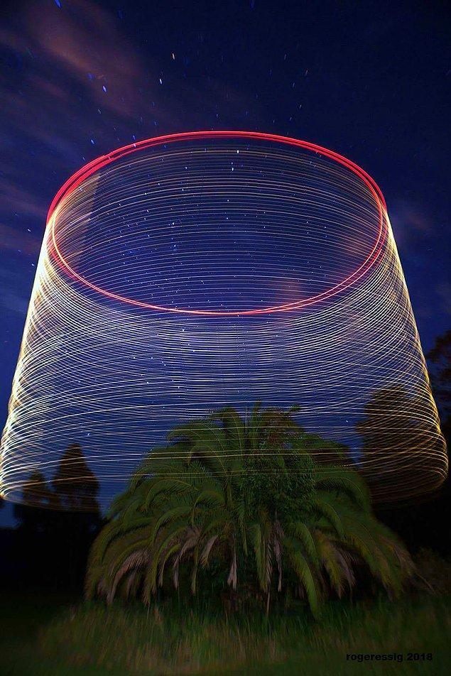 14. Bu fotoğraf drone, üzerine sabitlenen ışıklarla dönerek yükselirken, yavaş pozlamayla çekilmiş.