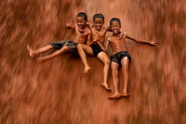 12. Jakarta'daki çamurlu tepelerden kayan üç çocuk.