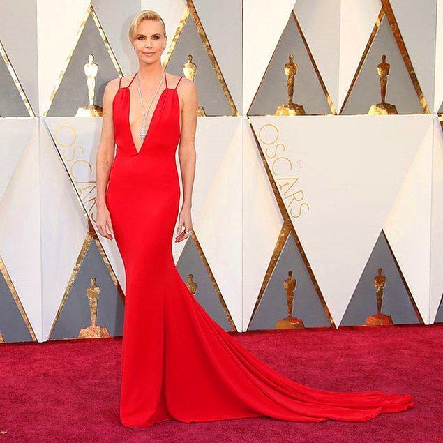 22. Charlize Theron derin bir göğüs dekolteli elbise ve dekoltesine doğru uzun parıltılı bir kolye tercih etmiş.