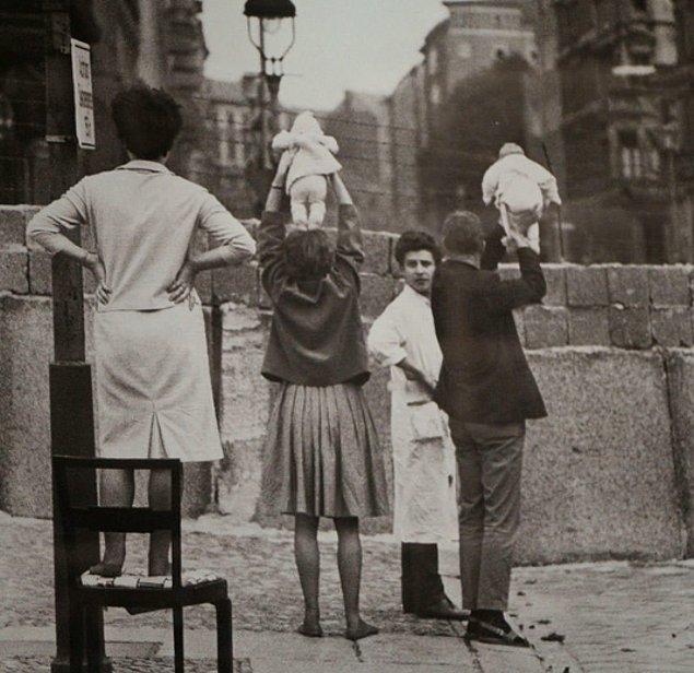 Berlin'in batı tarafındaki insanlar çocuklarını doğuda kalan anne ve babalarına gösterirken, 1961.