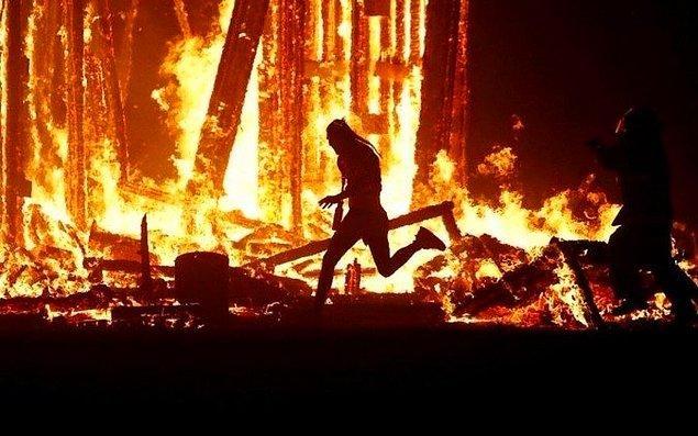 24. Burning Man Festivali'nde, yakılan ahşap kuklanın ortasına atlayan adam.