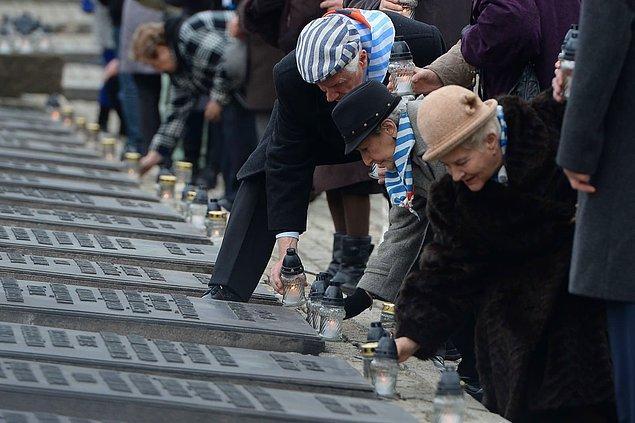 Auschwitz Kampı sağ kalanları, 27 Ocak 2016'da aileleriyle birlikte Oswiecim, Polonya'daki Kurbanlar Anıtı'na mum bırakıyor.