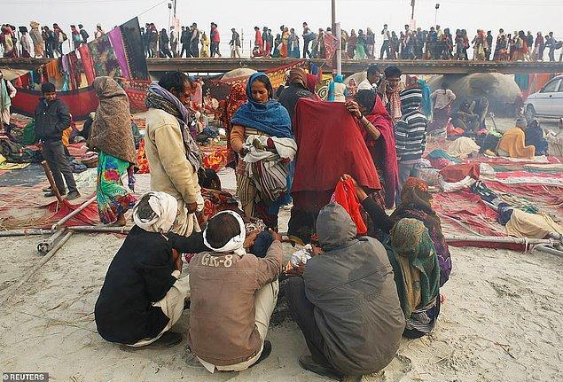 Kutsal dalışın ardından ateşin çevresinde kıyafetlerini kurutan insanlar.