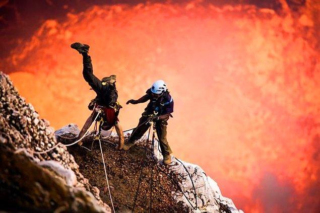 Aman aman, bu halatlı dağcı aktif bir yanardağın içinde dururken amuda mı kalkıyor öyle?