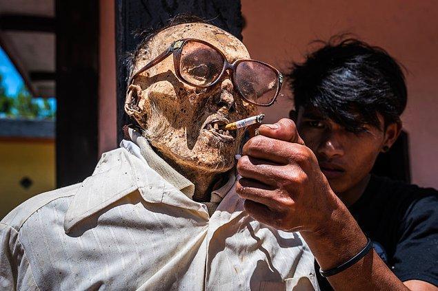 Bir genç, atasına sigara uzatıyor.