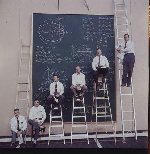 9. NASA bilim insanları hesaplamalar yaptıkları tahtanın önünde poz veriyorlar.
