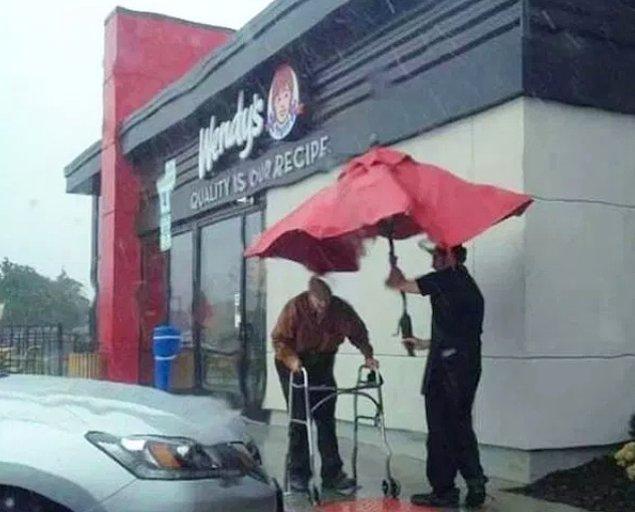 25. Yaşlı müşterilerine masa şemsiyesiyle yardım eden bir Wendy's çalışanı...