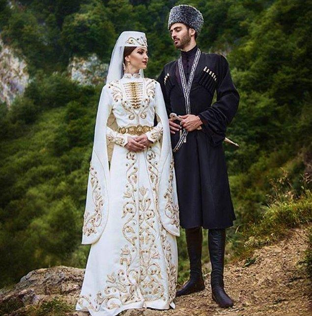 12. Kuzey Osetya-Alanya'daki gelinler, desenli uzun kollu elbise giyer ve bellerine tılsım olarak bilinen bir kemer takar.