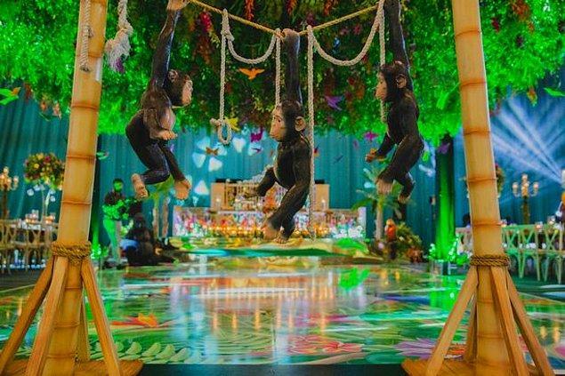 Tropikal papağan, goril ve ağaç heykelleri ile dans pisti süslenirken, üç küçük oyuncak maymun da iki tahta direğe bir iple bağlandı.