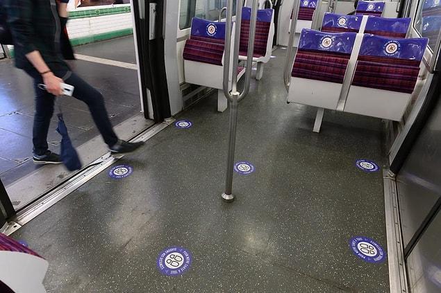 Paris'teki bir metroda güvenli sosyal mesafeyi gösteren çıkartmalar.