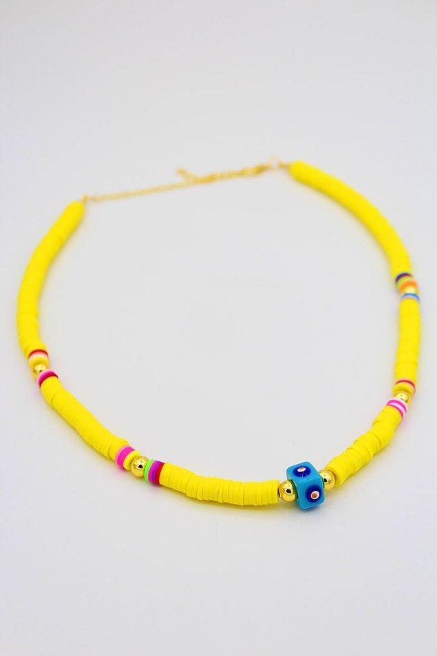 5. Neon sarı kolye, nazar boncuğu ve gümüş detayları ile öne çıkıyor.