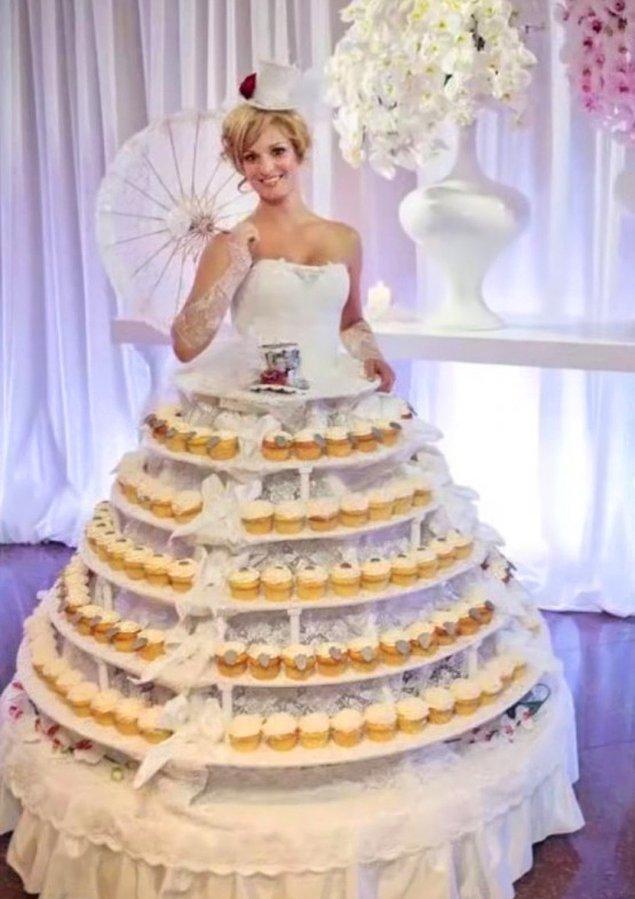1. Gelinin düğün pastası olduğu nadir düğünlerden biri! Bu gelinliğimiz kat kat etek görünümünü minik keklerden oluşturarak, dünyanın en kötü gelinlikleri listesinde yer almayı başarıyor. 😬