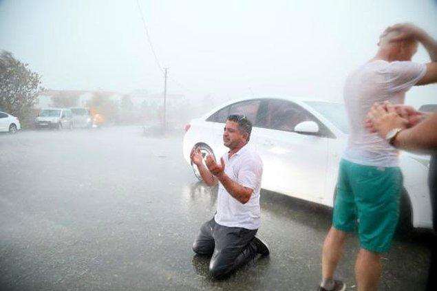 Kalemler Mahallesi'nde bir vatandaş, asfaltta dizlerinin üzerine çöküp yağmur altında dua etti.
