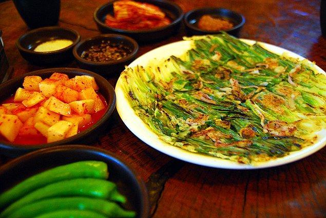 """6. """"Yeşil soğanlı pankek olan pajeon isimli yiyeceği sadece yağmurlu günlerde yiyorlar. Bu yemek farklı tür sebzelerle ve hatta deniz ürünleriyle de yapılabiliyor."""""""