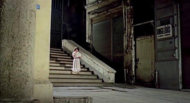 """Filmin sonunda Cüce'nin sokakta öldüresiye dövülüp yerde yattığı sahnede Cüce bir düdük sesiyle annesinin geldiğini hayal eder. Annesinin küçük halini gördüğü merdivenlerin yanında """"Angelidis"""" isimli bir dükkan tabelası kadraja girer. Bu dükkan gerçekte bir cenaze levazımatçısıdır. Yönetmen kara haberi bize orada bu detayla duyurur aslında."""
