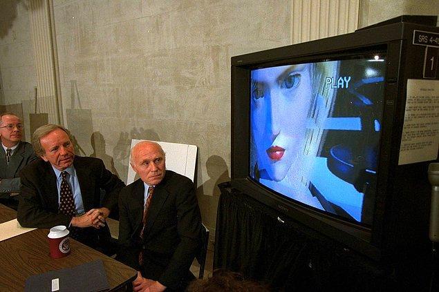 13. Senatör Joe Lieberman ve Senatör Herb Kohl video oyunlarının derecelendirilmesi ile ilgili bir oturumun ardından basın toplantısında bir oyunun videosunu izliyorlar. -1996